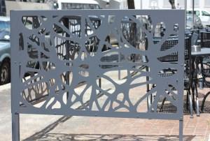 serie de balustrade legate avand decupate forme geometrice si care margineste o alee
