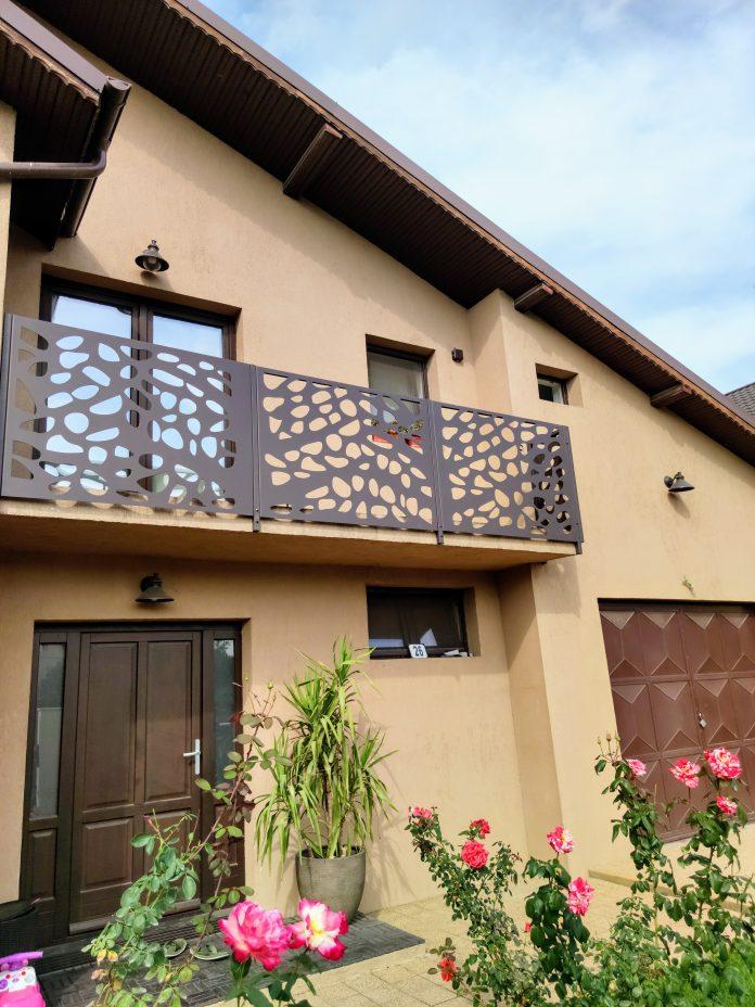 balconul unei case cu balustrada traforata vopsita maro inchis