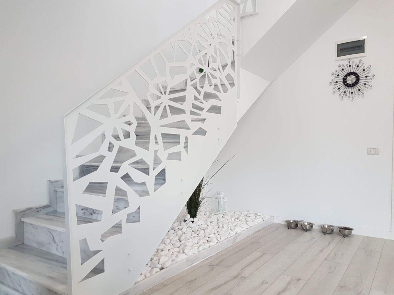 balustrada decorativa traforata alba la o scara interioara cu trepte marmura