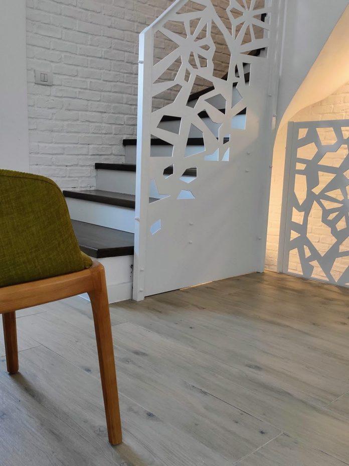 scara interioara cu balustrada metalica alba si trepte din lemn vopsite maro