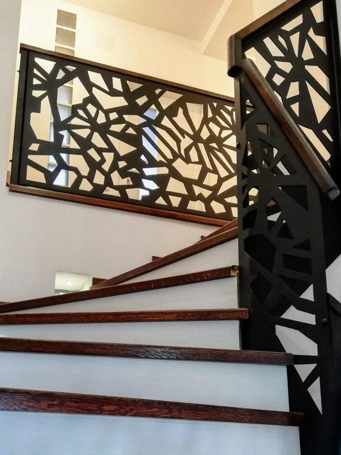 scara interioara cu trepte lemn stejar si balustrada decorativa metalica cu mana curenta lemn baituit maro