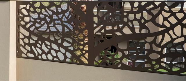 Prim plan cu un panou traforat gard cu soclu beton zugravit avand pe fundal fatada casei vopsita in aceeasi nuanta