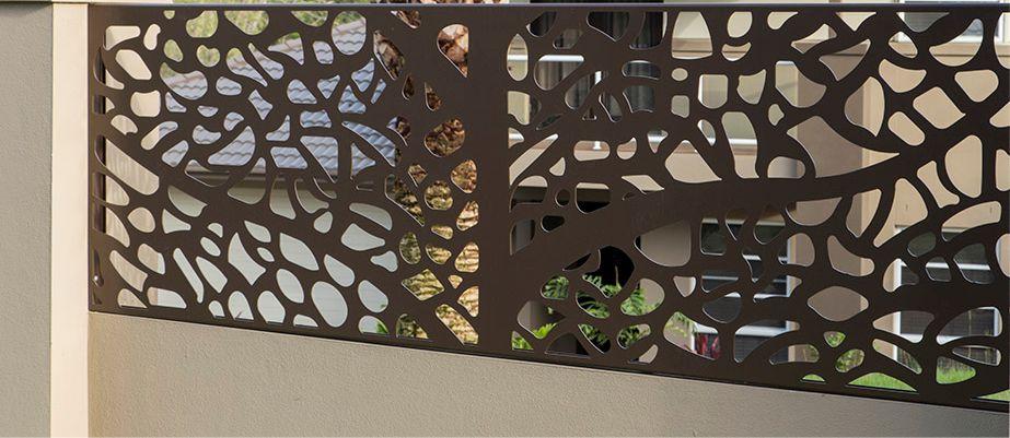 Soclu gard realizat din beton si panou metalic gaurit prin care se vede curtea si fatada casei.