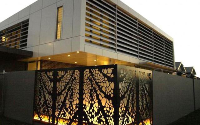 protejarea unei proprietati private cu gard inalt si panouri din otel cu gauri prin care difuzeaza o sursa de iluminat