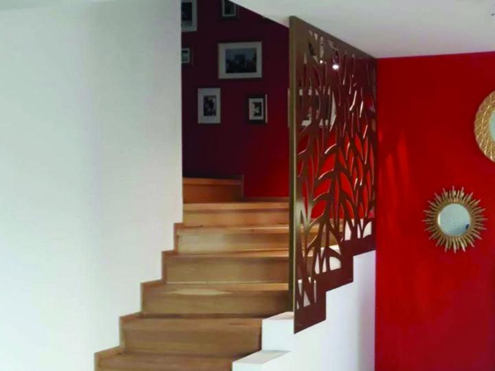 parapet decorativ metal auriu la o scara interioara cu trepte din lemn