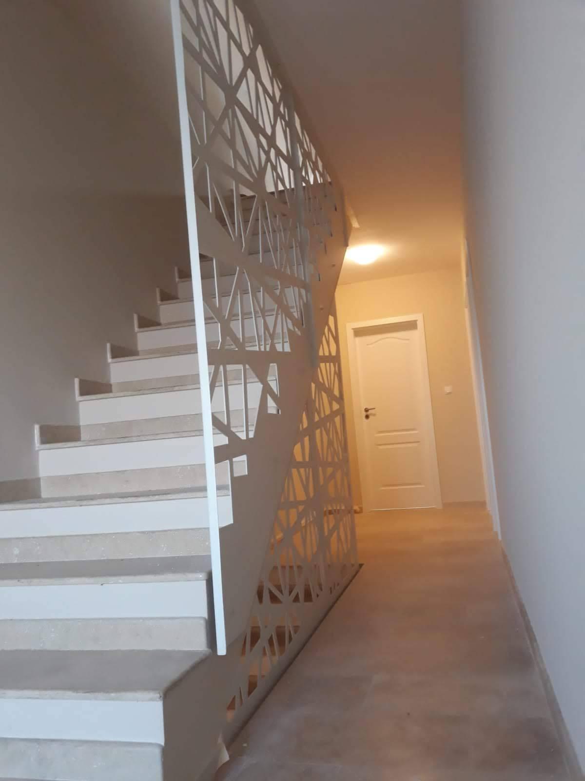 panou decorativ metalic alb pe post de parapete la o scara interioara