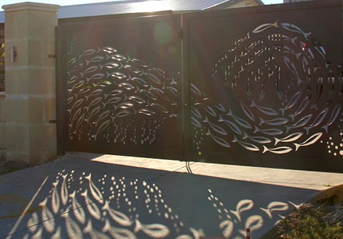poarta metalica dubla de intrare in curtea unei vile avand decupaje cu model de pesti