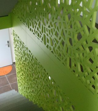 scara interioara incadrata de paravane traforate care formeaza perete de protectie