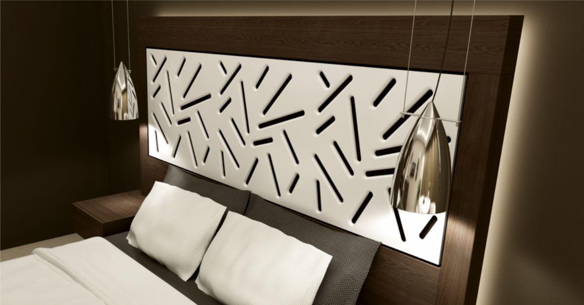 imagine pat dormitor cu tablie decorativa de culoare alba in care au fost traforate forme liniare